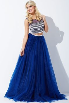 Creating a ball gown silhouette, this Jovani JVN30023 two-piece prom dress pairs a sleeveless cropped top with a full-length skirt in shimmer tulle. Horizontal metallic beading adorns the top which features a Sabrina neckline and V-back. The layered, gathered skirt has a beaded waistband.