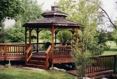 A gazebo with a walkway which attaches to a deck. The gazebo and bridge span the water.