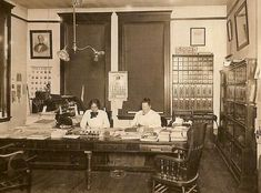 """Office with two women working at a long desk, 1914.  There is a Hotchkiss No. 1 stapler on the desk, an interesting file cabinet, and a set of three glass front sectional bookcases."""