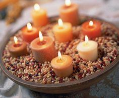 Autumn Candleholder - This autumn-color centerpiece is perfect for the Thanksgiving table or any autumn gathering. Best of all, it looks great even without the candles lit. Simply fill a shallow bowl with unpopped popcorn kernels and dried beans. Nestle votive candles into the mixture until they are stable. Be sure the mixture isn't too close to the candlewicks