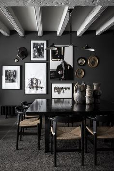 Stunning, all-black dining room makes a statement, featuring dark walls, black and white art gallery along the wall, black and straw dining chairs and assorted vases for added style | Maison Hand