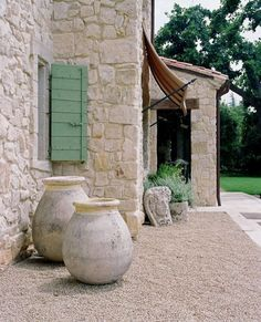 French Mediterranean patio.  Love the big stone vessels.