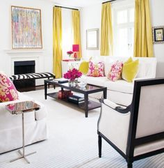 White livingroom with classic chic black and white furniture.  Thong yellow drapes and yellow and pink color and pattern throw pillows add bright touches of color to the space.  The extra pops of brightpinkfromthevase of flowers and the candle  table tie everythingtogether.The watercolor print over the fireplace incorporate all the accent colors in a softer palette.