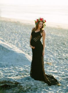 a sheer black dress that shows off the baby bump accented with a flower crown