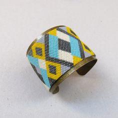 Manchette Peyote en perles de verre japonaises tissées à laiguille.    Mélange de teintes brillantes et mattes, formes géométriques et couleurs