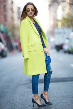 Loving this citron double-breasted coat on Denise from Coloristta. She styles it over a pair of distressed skinny jeans and a gray v-neck sweater. She finishes the look with a pair of black pumps and a bright blue purse | Banana Republic