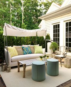 outdoor living space | settee with canopy + upholstered ottomans with nailhead + natural elements