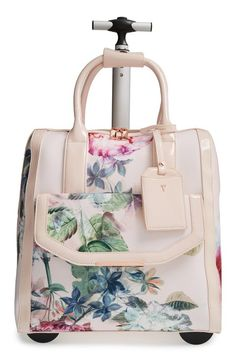 With its gorgeous floral print and rose gold-toned hardware, this travel bag turns any getaway into a stylish event. A deep interior holds everything you need for the journey, while an exterior pocket keeps necessities close at hand. Two swivel wheels and a telescoping handle keep you rolling along, while dual top handles make this bag easy to pick up and tote. A luggage tag with the T logo is included. Zip-around closure. Top carry handles; telescoping handle. Exterior snap pocket…