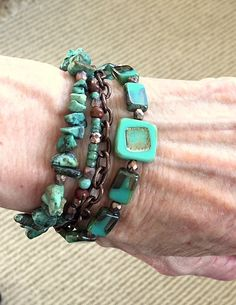 This multistrand bracelet measures 7 inches and has a 1 1/2 inch chain extension. One strand is made of beautiful hand made Czech glass beads with beautiful turquoise, gold and amber shades running through the glass. Small faceted matte gold and copper color spacers pick up the colors of the beads. Another strand is African turquoise with the same spacers. The third strand is made with various Picasso finished Czech glass beads, wood beads and the faceted spacers. The fourth strand is a…
