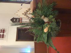 Palm Sunday Arrg - An interpretive design featuring woven emerald palm to represent the two fish, along with bread to symbolize the  feeding of the 5,000, a vessel and grapes to symbolize the water turned to wine at Cana; all representing  miracles performed during Christ's ministry. The array of palm shows Jesus' triumphant entry into Jerusalem at the start of Passover, the woody fan willow represents the cross, the white  catkins of the pussy willow represent Christ as the sacrificial…