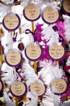 Who says escort cards must be rectangular? Think outside the box and design your escort cards into different shapes. Use either gold or white feathers for each card, and place onto a small tree or another similar alternative to hang each card.