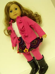 The outfit includes a pink ruffled sweater, white sleeveless top, corduroy skirt, leggings, and boots. The sweater, leggings, and top are all made from prewashed t-shirt knit. The top is fully lined and has a velcro closure in the back. The leggings have elastic in the waist. The lightweight corduroy skirt is a fun print which includes peace signs and other colorful designs on a black background. It has an elastic waist and ruffled pink tulle under the skirt. The corduroy was prewashed prior…