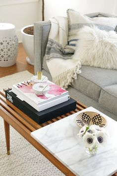 Soft, grey sofa and throws with a perfect mid-century coffee table. Beautiful coffee table styling, too!