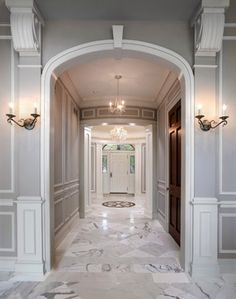 love the idea of a small entrance that leads into a big foyer with grand staircases