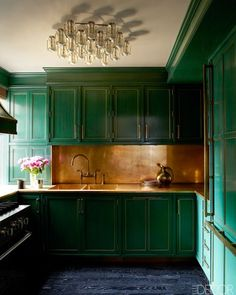 Star Kitchen: Cameron Diaz's Manhattan kitchen. Rich green cabinetry is vibrant against brass backsplash, counters, and sink.