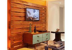 Paletes de madeira viraram um painel para a televisão. Projeto da arquiteta Estela Pinheiro