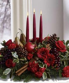 JOYFUL AND TRIUMPHANT - Adorn your table with this beautiful centerpiece arranged with fresh flowers, fruit and evergreens with three tall red tapers. Perfect for your holiday table.