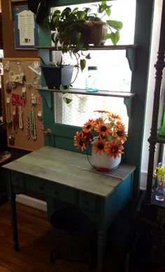Repurposed an old door into a gardening table. Could also be used indoors as a desk! We used an old sewing machine cabinet, replacing the top with old wood. Added chicken wire to openings where glass was broken, along with matching shelves. Finished and sold this piece on the same day!