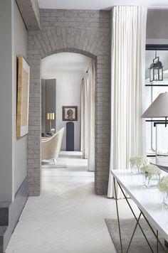 Brick painted gray, draperies ceiling mounted, nice flooring.