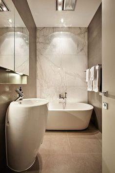The bathtub in front of this marble wall is the center of this narrow but beautifully designed bathroom. | Die Badewanne vor dieser Marmorwand ist das Zentrum dieses schmalen, aber wunderschön gestalteten Badezimmers. #bathroom #bathtub #marble #badezimmer #badewanne #marmor