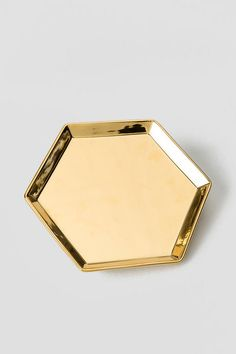 """Nothing+accessorizes+a+home+or+apartment+like+gold!+The+GoldHexagonTraycan+be+used+for+entertaining+or+decorating.+Serve+your+favorite+little+snacks+to+guests+or+store+your+favorite+jewelry+on+your+vanity.+Thistray+is+gorgeous&+functional!<br+/>  <br+/>  -+8.5""""+x+8.5""""<br+/>  -+Gold+painted+ceramic<br+/>  -+Hand+wash+only<br+/>  -+By+Rosanna<br+/>"""