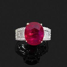 """BAGUE JONC PLAT <br>en or gris, ornée d'un beau rubis ovale """"sang de pigeon"""" pesant 6,60 cts, l'épaulement agrémenté d'une chute de diamants baguettes soulignés d'un pavage de diamants ronds. <br> <br>Dimensions de la pierre : 13,46 x 11,06 x 5,18 mm. <br> <br>Poids : 8,5 g. <br> <br>A diamond and 18K gold ring set with an oval shaped """"pigeon's blood"""" ruby weighing 6,60 cts. <br> <br>La pierre accompagnée d'un certificat G.R.S. attestant : origine Mozambique, couleur rouge vif ..."""