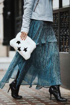 Veja os detalhes do look de Luiza Sobral no desfile Burberry no London Fashion Week. Casaco de couro azul bebê, clutch branca de pelinhos, saia longa esvoaçante e bota de cano alto preta de bico fino.