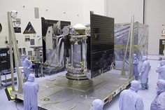 NASA's OSIRIS-REx spacecraft is revealed after its protective cover is removed inside the Payload Hazardous Servicing Facility at Kennedy Space Center in Florida. The spacecraft traveled from Lockheed Martin's facility near Denver, Colo., to Kennedy to begin processing for its upcoming launch, targeted for Sept. 8 aboard a United Launch Alliance Atlas V rocket. Image: NASA/Dimitri Gerondidakis