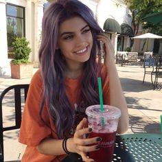 Chica sentada tomando un café de starbucks y sonriendo