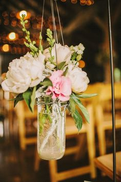Pretty aisle marker made with a hanging mason jar full of flowers #wedding #diywedding #rustic #ceremony #flowers