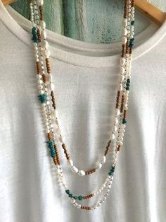 White Freshwater pearls, turquoise nuggets and tiny tan wooden beads hand knotted on silk. Can be worn long or as two shorter strands. This long beaded necklace makes a great summer accessory. This necklace is about 36 inches long and looks great casually draped on its own or layered with other pieces. Can also be wrapped around the wrist and worn as a bracelet. Layered in the 4th and 5th picture with these necklaces…