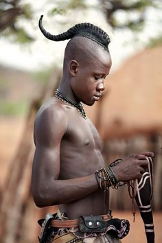 Himba Youth Has His Hair Styled in a Long Plait known as 'Ondatu'. Namibia. Photographer Nigel Pavitt