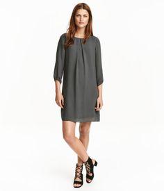 Donkergrijs. Een jurk van chiffon met een rechte pasvorm. De jurk heeft een…