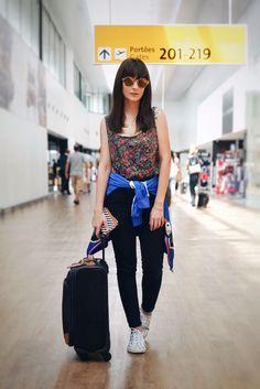 Look da Danielle Noce para viajar: calça preta, regata florida, jaqueta e tênis.