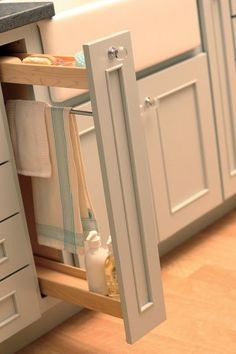 Personal Touches - This thin pull-out next to the sink has a towel rod so dish towels can dry after use #traditionalkitchens