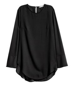 Black. Blouse in airy woven fabric. Opening at back of neck with button, long sleeves with wide cuffs, and rounded hem with slits at sides. Longer at back.