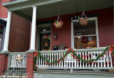 christmas front porch GARLAND shoved into the hanging baskets with ornaments wrapped onto garland