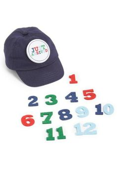 """This Mud-pie baseball cap captures baby's growth from """"just arrived"""" to 12 months with interchangeable felt numbers! Great accessory for monthly photo journals and the latest social media sharing trend. It is a perfectnew-mom or grandma shower gift. One size, 0-12 month. Milestone Baseball Cap by Mud Pie. Home & Gifts - Gifts - Gifts by Occasion - Baby & Kids Florida"""