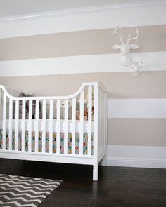 khaki and white striped nursery wall, faux animal heads, chevron rug