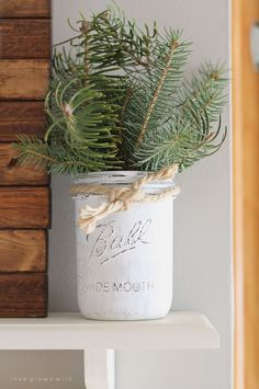 Use a distressed-white Mason jar, bits of evergreen, and some rope to add visual interest to a kitchen shelf. See more at Love Grows Wild.    - CountryLiving.com