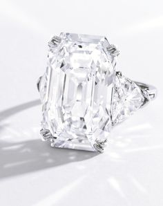 Highly Important Platinum and Diamond Ring, Harry Winston Centered by an emerald-cut diamond weighing 19.51 carats, flanked by two triangle-shaped diamonds weighing 2.92 carats