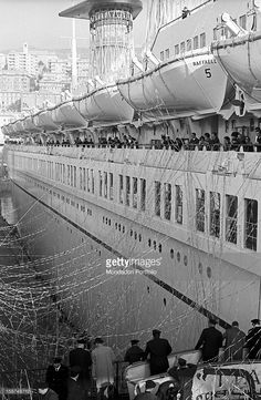 Passengers on the decks of the Raffaello transatlantic liner greeting before sailing to New York. Genoa, 6th December 1965