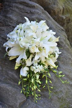 All-white cascading bridal bouquet with calla lilies, orchids, roses and lilies. / Photo by jessicaschmittphotography.com