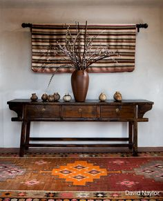 An antique Chinese chest, Indian pots, a Guatemalan wall weaving, and the Turkish kilim rug blend well, as their color schemes are similar. Note the rug's pleasing combination of pink, purple, orange, and rust.