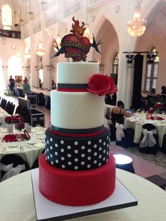 Spectacular wedding cake with a Rockabilly theme. Black and red, polka dots, and an amazing tattoo topper. By Crummb, Singapore.