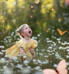 Cute little girl watching butterflies fly around a flower field.