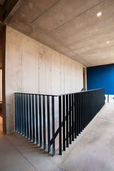 The elegant simplicity of the balustrade detail was created by casting the vertical steel flat bars of the balustrade directly into the concrete floor, creating a smooth and uncluttered finish.: