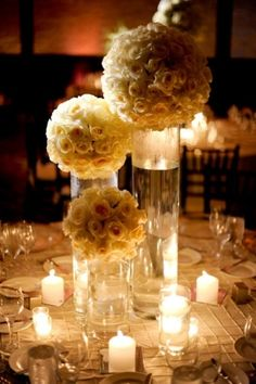 Candles, cylinder vases filled with water and rose kissing balls centerpieces