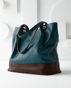 We're touting our newest leather tote made just for us in a little pelletteria in the hills of northern Italy. In a range of rich colors, color-block options, and calf hair, the modern shape pinches in slightly at the sides with cool O-ring hardware at the shoulder straps.