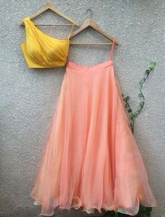 Indian lehenga outfit yellow one off shoulder blouse with peach lehenga Indian Gowns Dresses, Indian Fashion Dresses, Dress Indian Style, Indian Designer Outfits, Indian Outfits, Indian Designers, Lehenga Choli Designs, Indian Lehenga, Silk Lehenga